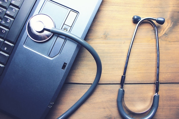 Stethoscope on paper.notebook and pen on wooden table