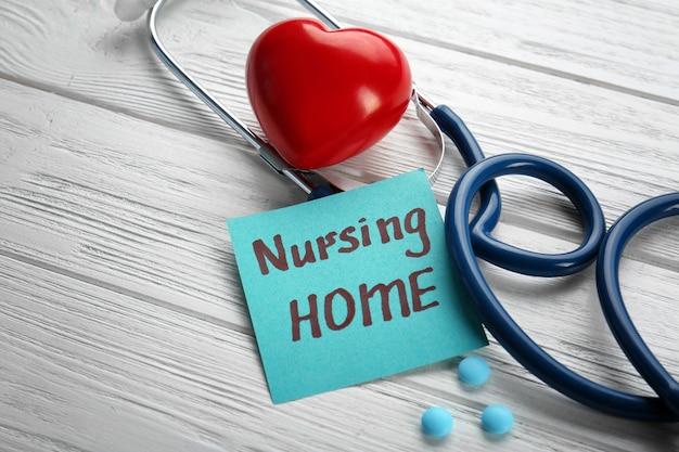 Stethoscope and paper sheet with text nursing home on wooden background