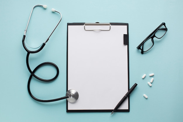 Stethoscope and pen on clipboard near pills with spectacles over blue surface