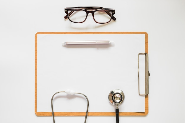 Stethoscope; pen and eyeglasses on clipboard with paper over the white background