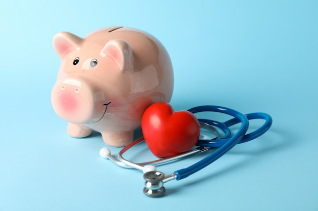 Stethoscope and piggy bank on blue background, space for text