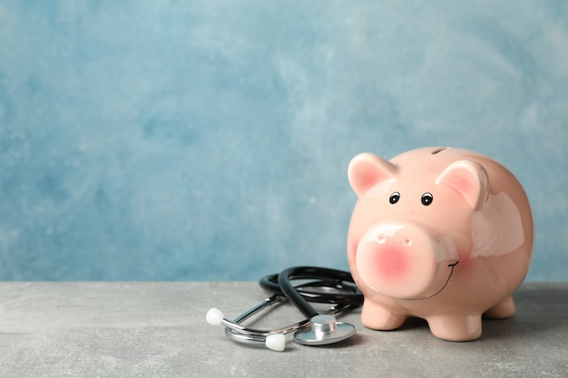 Stethoscope and piggy bank on grey background, space for text