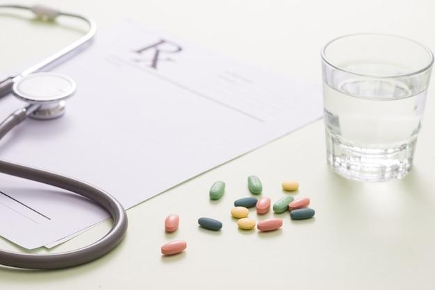 Стетоскоп, таблетки и стакан воды на светло-зеленом фоне. концепция медицины