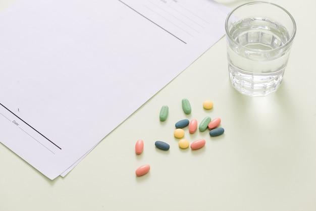 Стетоскоп, таблетки и стакан воды на светло-зеленом фоне. концепция медицины Premium Фотографии