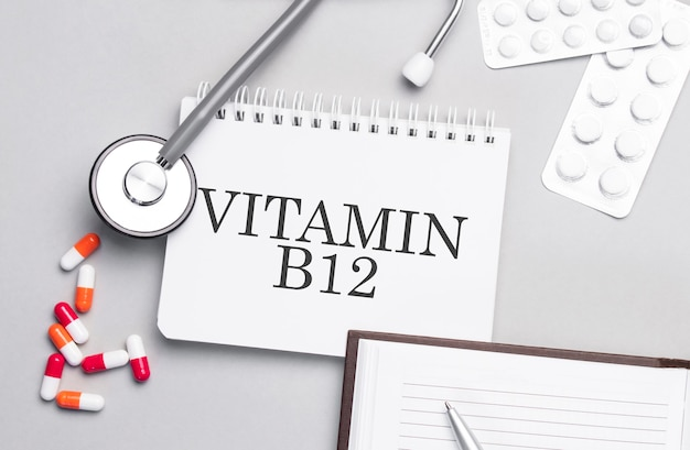 청진 기, 환 약 및 의료 테이블에 비타민 b12 텍스트와 노트북.