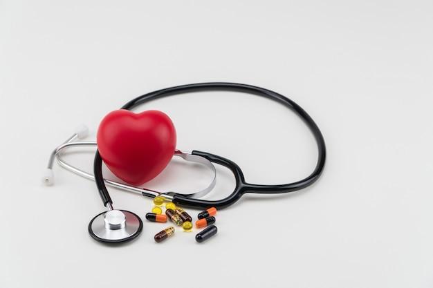 聴診器、錠剤、おもちゃの心臓。コンセプトヘルスケア。心臓病学-心臓のケア