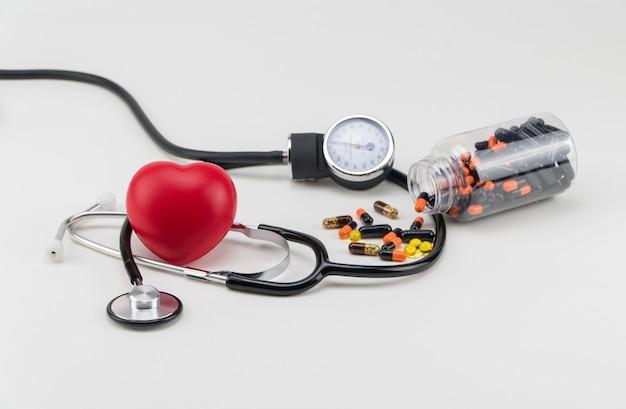 聴診器、ピル、おもちゃの心臓。コンセプトヘルスケア。心臓病学-心臓のケア