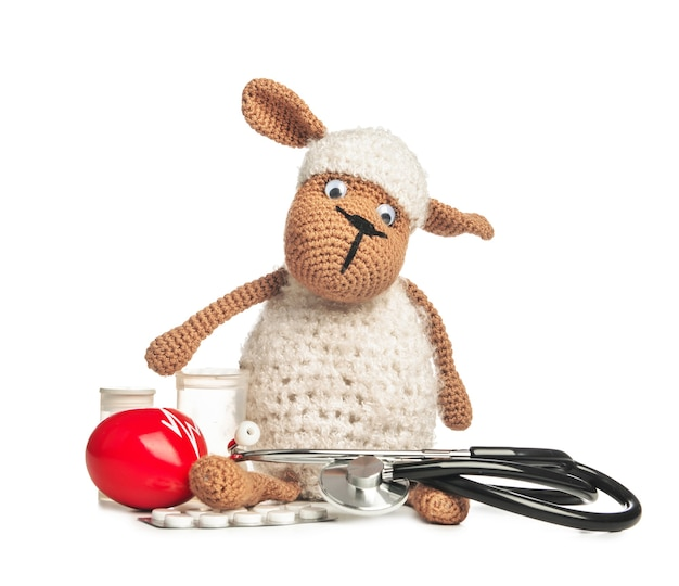 Stethoscope, pills and baby toy on white