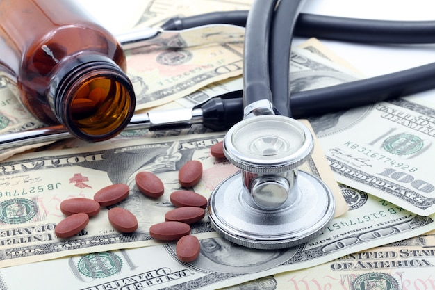 Stethoscope and pills on dollars