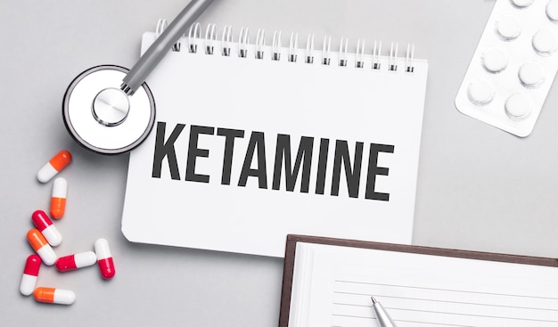 Stethoscope, pills and notebook with ketamine text on the medical table