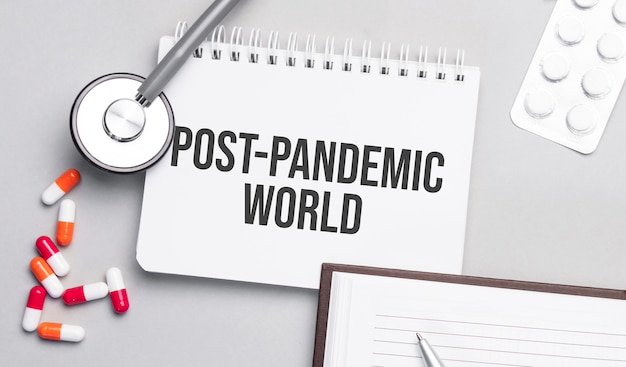 Stethoscope, pills and notebook with post pandemic world text on the medical table