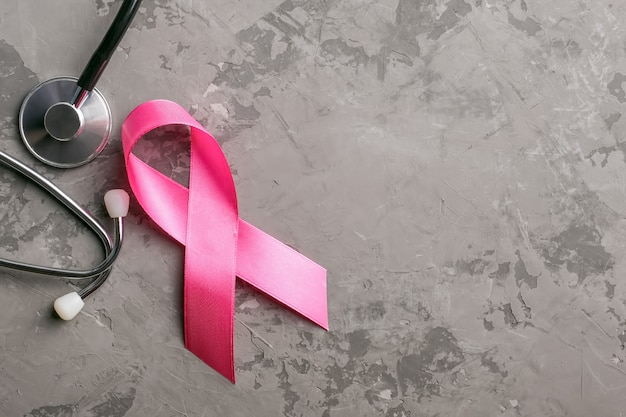 Stethoscope and pink ribbon on concrete background