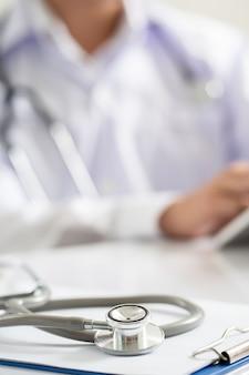 Стетоскоп размещен на столе врача в больнице.