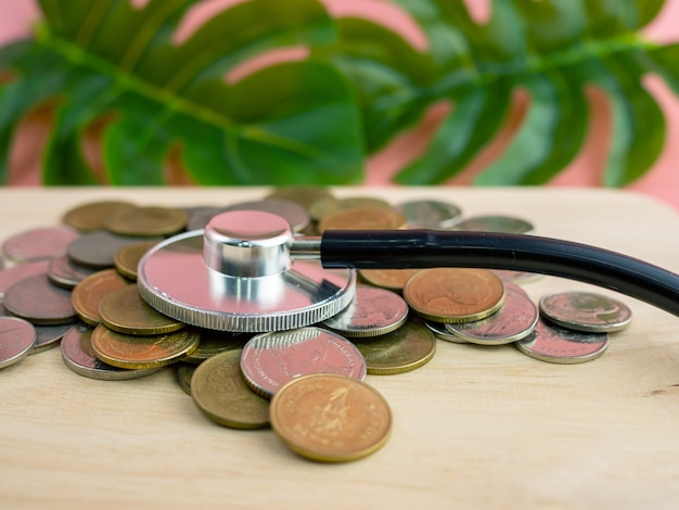 A stethoscope placed on a pile of money is a financial exam concept