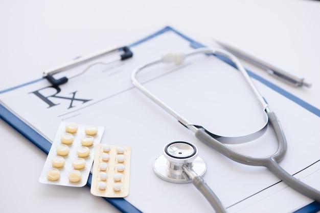 コピースペースのある白い表面に聴診器、処方クリップボード、錠剤のボトル。ヘルスケアと医療の概念。