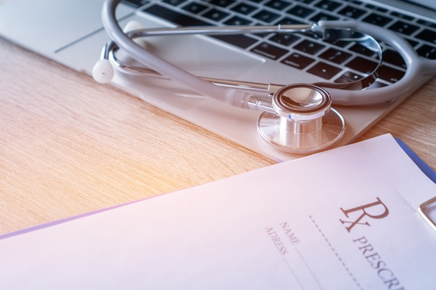Stethoscope and prescription clipboard with record information paper on laptop medicine