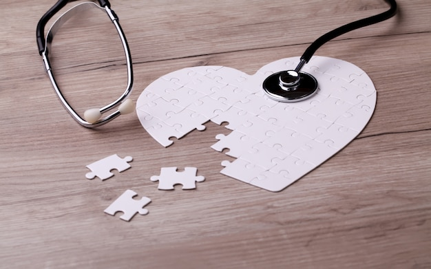 Stethoscope on puzzle, solving the mystery of health care