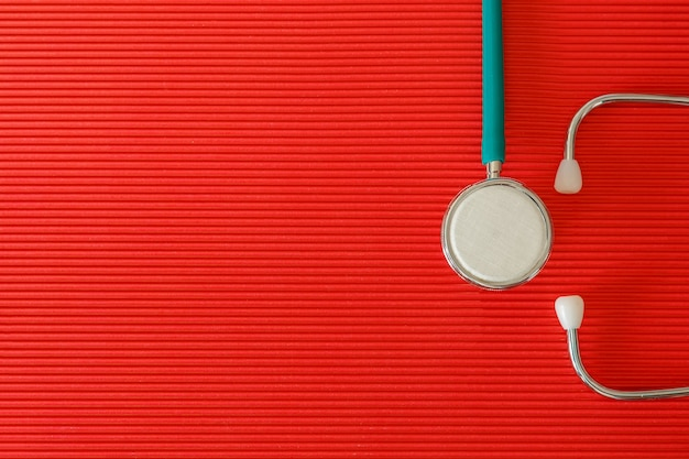 Stethoscope on a red background top view with free space