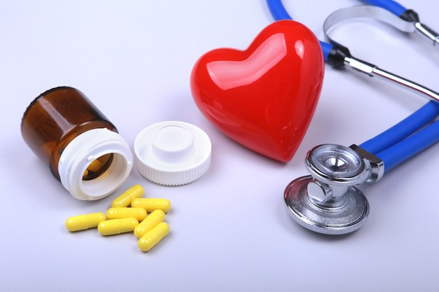 Stethoscope, red heart and assorted pills.
