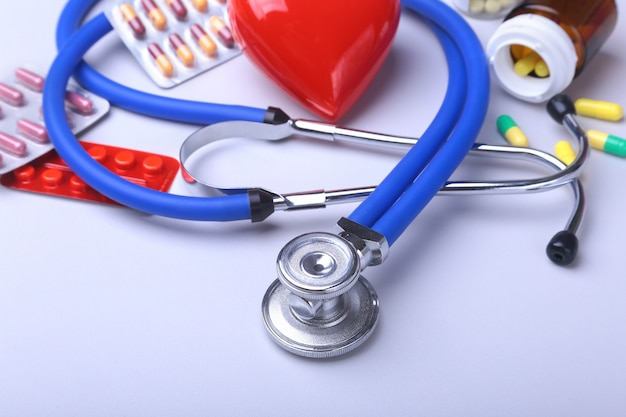 Stethoscope and red heart, colored pills, tablets, capsules blisters for pharmacy and medicine.
