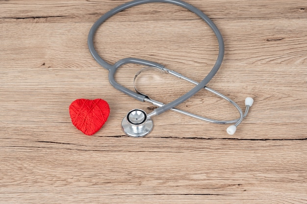 Stethoscope and red heart pace on the desk