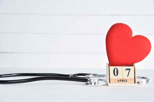 Stethoscope and red heart with april 7 text wooden block calendar on white wooden background.