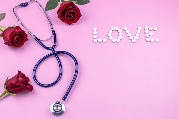 A stethoscope roses and the word love made up of pills