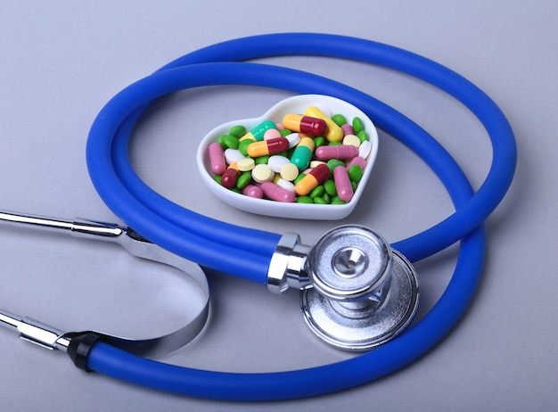 Stethoscope, rx prescription and colorful assortment pills and capsules on plate.