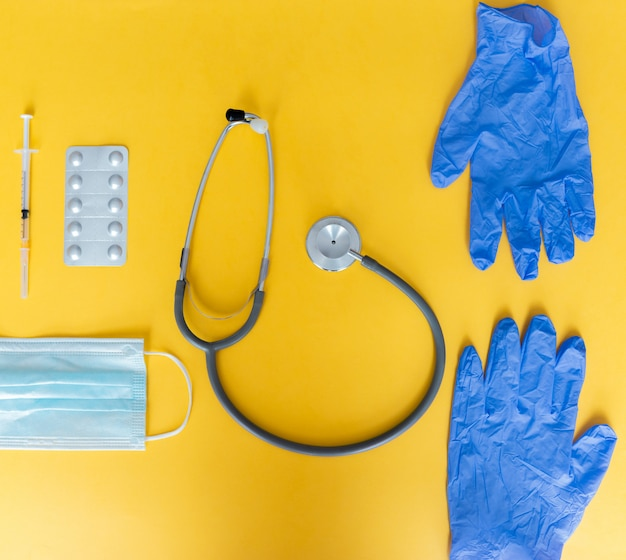 Stethoscope, syringe, latex gloves, face mask, and pills on yellow table
