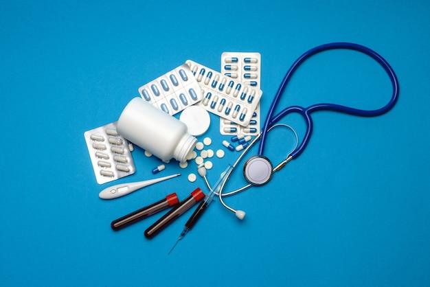 聴診器、注射器、体温計、血液検査管、およびコピースペースのある青い背景の上面図の丸薬の缶。