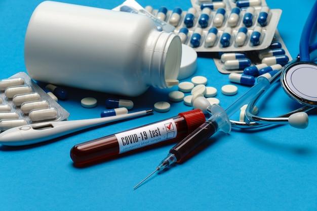 聴診器、注射器、温度計、血液検査管、青い背景の丸薬の缶上面図