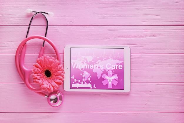 聴診器、タブレットコンピューター、木製のテーブルの花。婦人科の概念