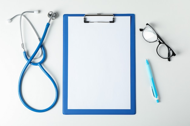 Stethoscope, tablet, glasses and pen on blue background, space for text