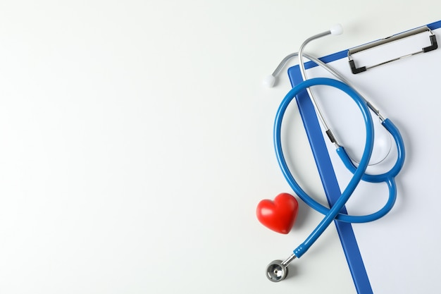 Stethoscope, tablet and heart on white background, space for text