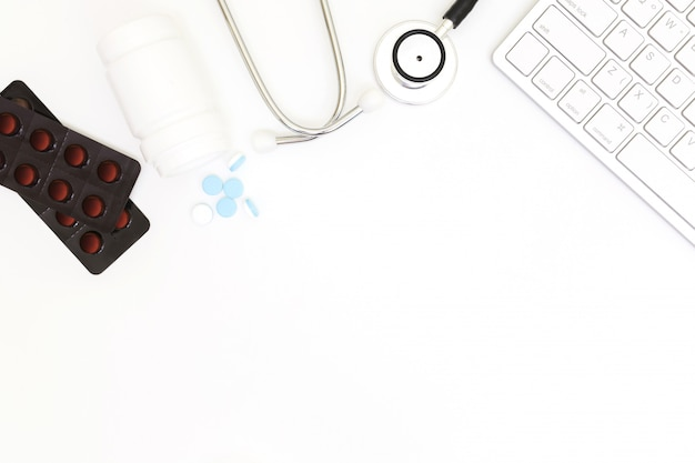Stethoscope, top view of doctor's desk table, blank paper on white background.