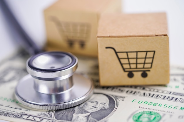 Stethoscope on us dollar banknotes with shopping cart box.