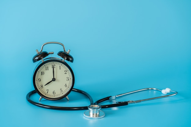 Stethoscope and vintage clock on blue space. medical and health care concept