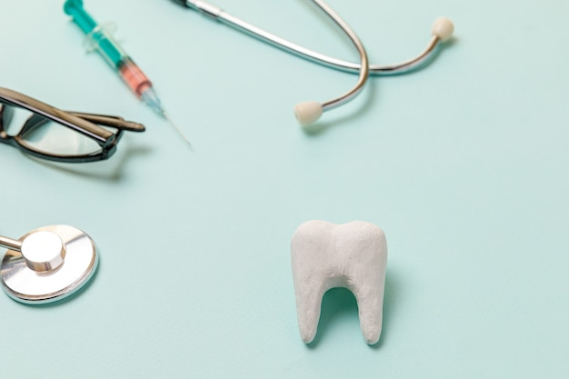청진기, 흰색 건강한 치아, 안경 및 주사기 파란색 배경에 고립