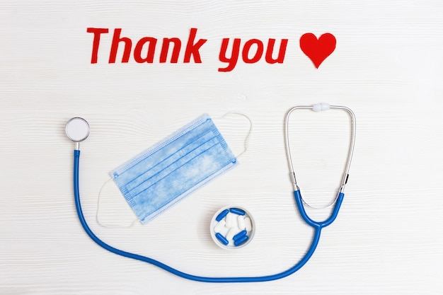 Stethoscope with blue colored pills red heart shape and thank you text