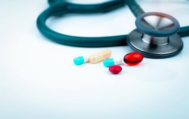 Стетоскоп с сине-белой капсулой, красными капсулами из мягкого геля и красными круглыми таблетками на столе врача или медсестры.