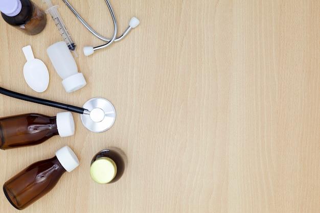 薬のボトル、木製のテーブルの背景に注射器を供給する聴診器。医学的背景の概念。
