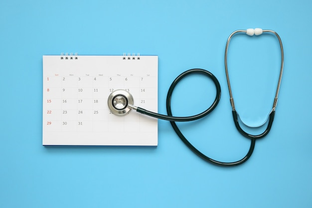 Stethoscope with calendar page date on blue background doctor appointment medical concept