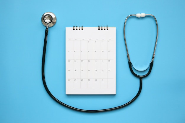 Stethoscope with calendar page date on blue table, doctor appointment medical concept