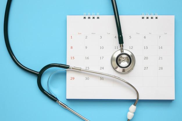 青いテーブル、医師の予定医療コンセプトにカレンダーページの日付の聴診器