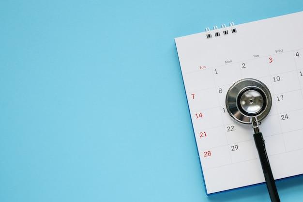 Стетоскоп с датой страницы календаря на синем