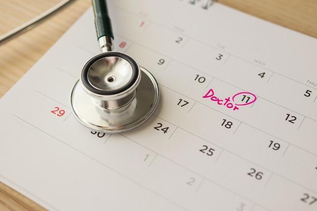 木製のテーブルの背景にカレンダーページの日付が付いている聴診器医師の予約医療の概念