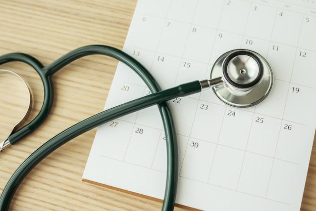 나무 테이블 배경 의사 약속 의료 개념에 달력 페이지 날짜와 청진 기