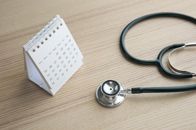 Стетоскоп с датой страницы календаря на фоне деревянного стола назначение врача медицинская концепция