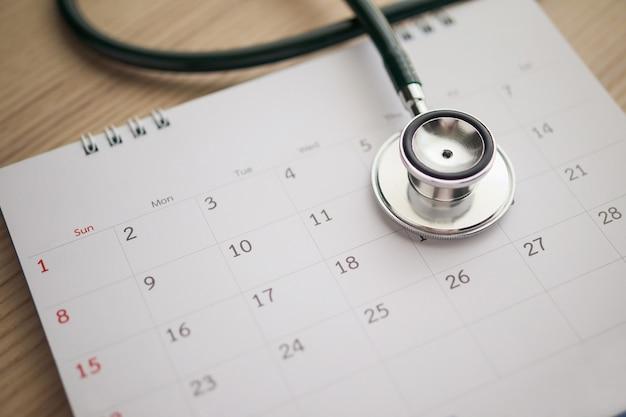 木製のテーブルの背景にカレンダーページの日付と聴診器医師の予約医療コンセプト