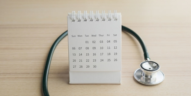 Stethoscope with calendar page date on wood table. doctor appointment medical concept